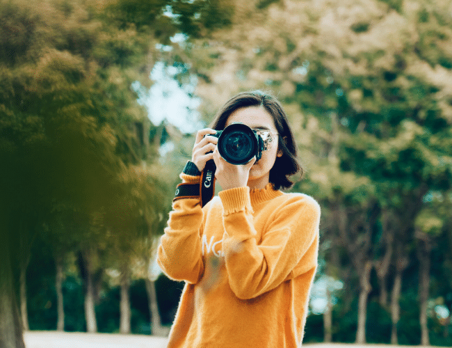 Woman in yellow sweater holding camera