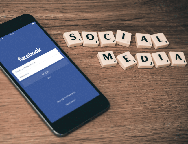 """Mobile phone with Facebook app and """"social media"""" spelled out in Scrabble pieces"""